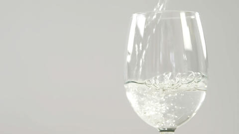 White wine falling in glass against white background Live Action