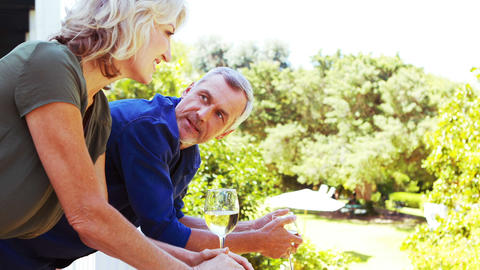 Mature couple interacting with each other while having wine in balcony Live Action