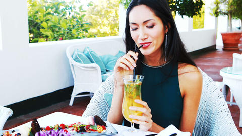 Beautiful woman drinking mocktail while having meal Live Action