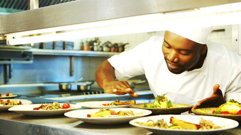 Chef garnishing meal at order station of commercial kitchen Live Action