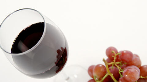 Close-up of red bunch of grapes with glass of red wine Live Action