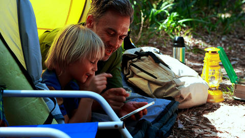 Father and son using digital tablet outside tent Live Action