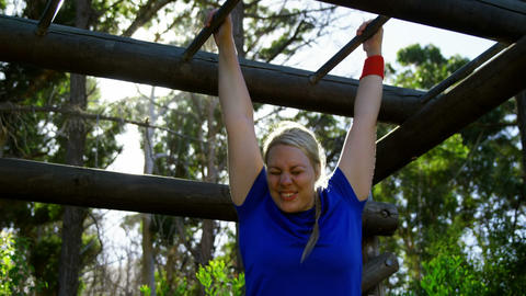 Determined woman exercising on monkey bar during obstacle course Live Action