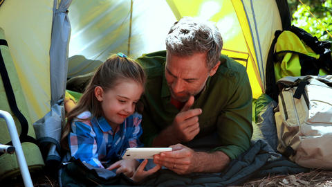 Father and daughter using mobile phone outside tent Live Action