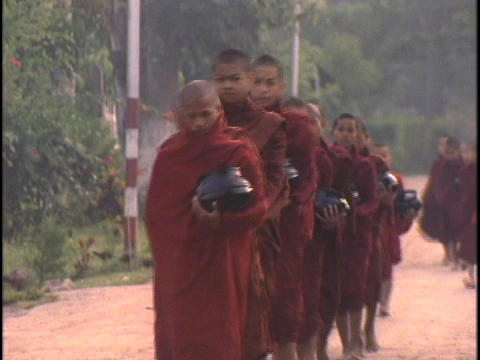 Buddhist monks collect alms in the morning Stock Video Footage