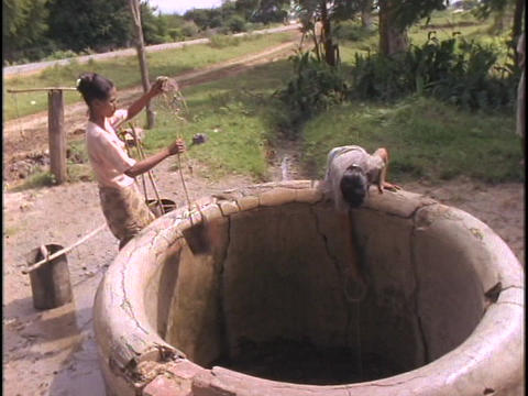Women fetch water from a well Stock Video Footage
