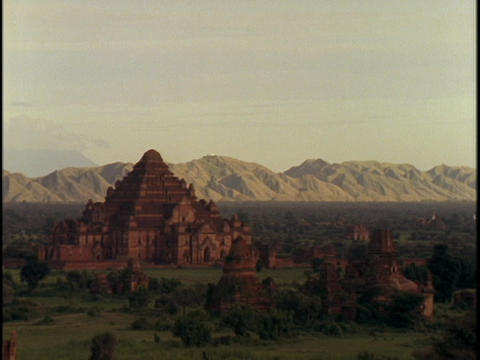 An ancient temple sits near mountains Footage