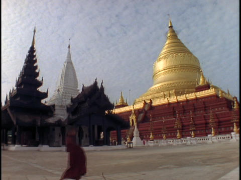 A pedestrian walks in front of a Buddhist temple in Burma Stock Video Footage