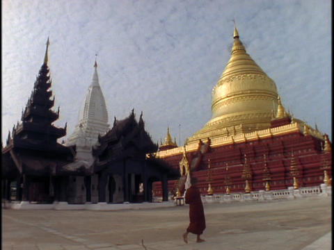 A pedestrian walks in front of a Buddhist temple in Burma Footage