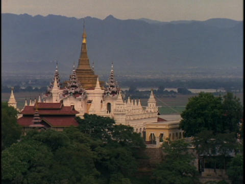 A beautiful, ancient Buddhist temple stands in front of a mountain range in Burma Footage