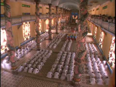 Worshippers kneel and pray inside the Cao Dai Temple Stock Video Footage