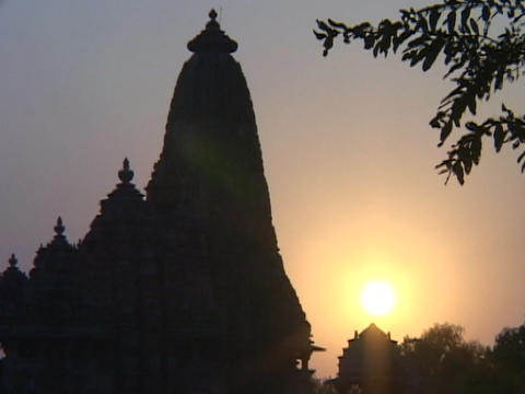 A spire on an Indian temple stands silhouetted against the sun Footage