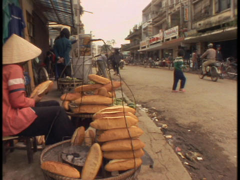 A Vietnamese peasant woman stacks loaves of bread at a food stand Footage