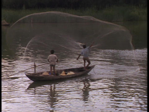 A Vietnam fisherman throws huge net from a canoe Live Action