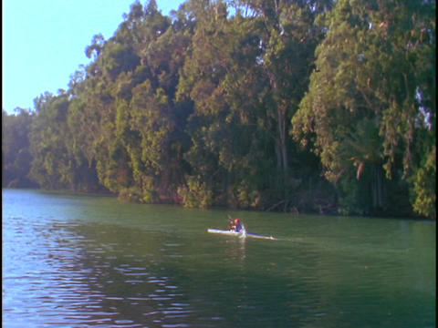 A woman kayaks down a river Stock Video Footage