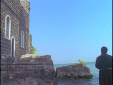 A Catholic priest stands and looks into the distance near the Sea of Galilee Footage