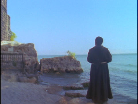 A Catholic priest stands and looks into the distance near... Stock Video Footage