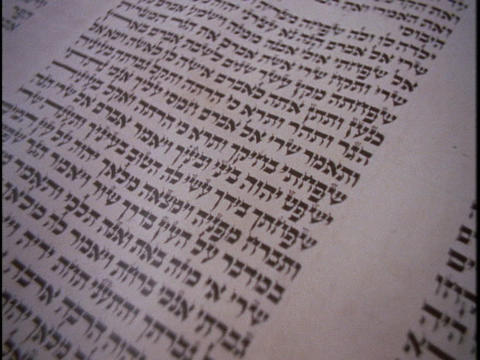 Ancient Hebrew letters cover a Torah scroll Footage