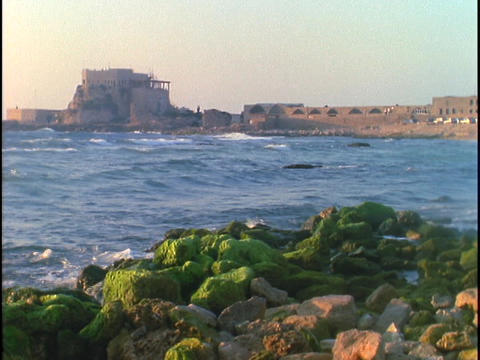 The sea crashes against the shore near ancient Roman ruins Stock Video Footage