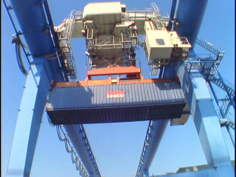 A machine loads containers onto trucks at a port Stock Video Footage