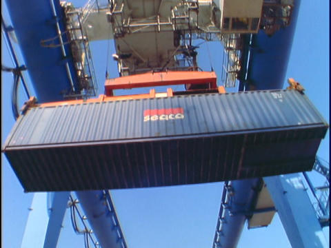 A machine loads containers onto trucks at a port Footage