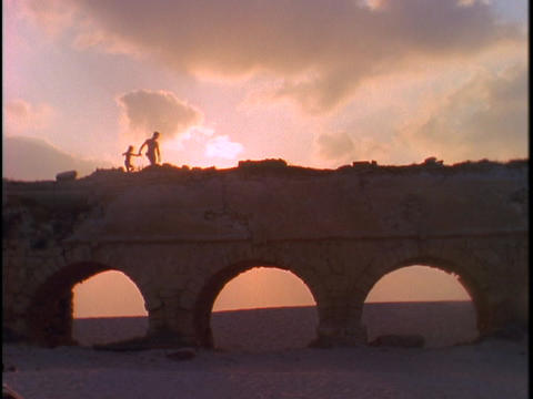 A father and daughter walk on an aqueduct Stock Video Footage