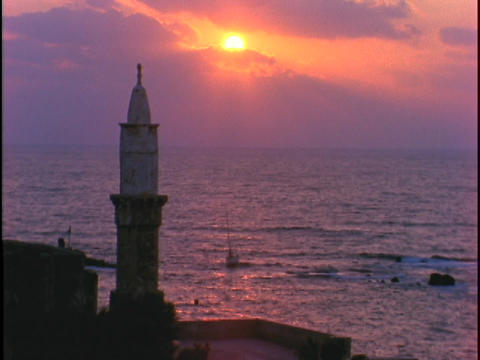 The sun sinks low over a mosque in Jaffa Footage