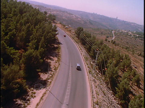 Traffic drives on a two lane highway in the mountains Stock Video Footage