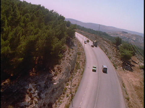 Traffic drives on a two lane highway in the mountains Footage