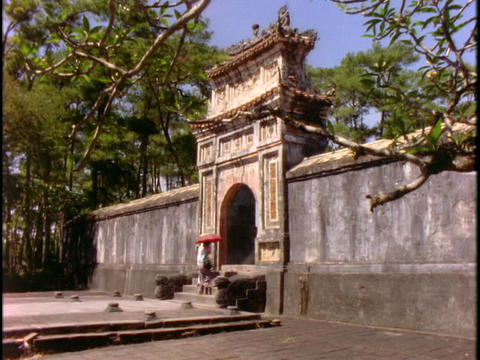 Pedestrians walk through a gate at a pagoda in Vietnam Live Action