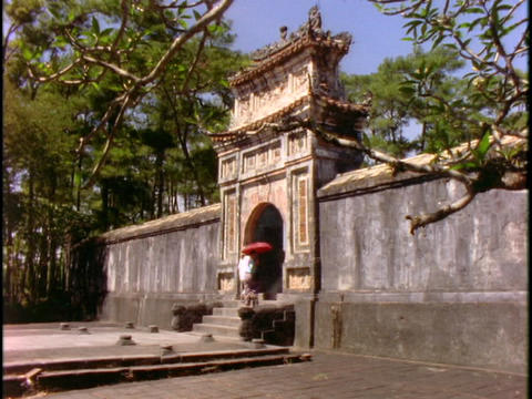 Pedestrians walk through a gate at a pagoda in Vietnam Stock Video Footage