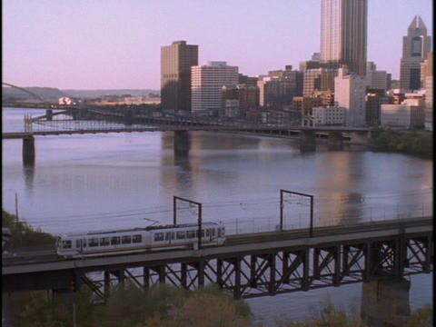 A transit train crosses a bridge in Pittsburgh, Pennsylvania Stock Video Footage