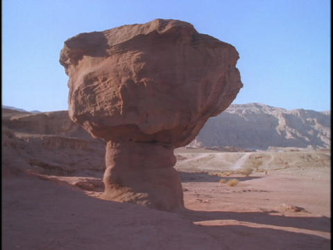 A rock formation in the desert resembles a mushroom Stock Video Footage