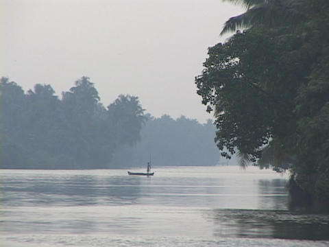 A man in a canoe poles across the river Stock Video Footage