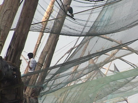 A man lounges beside fishing nets hanging in Kerala, India Footage