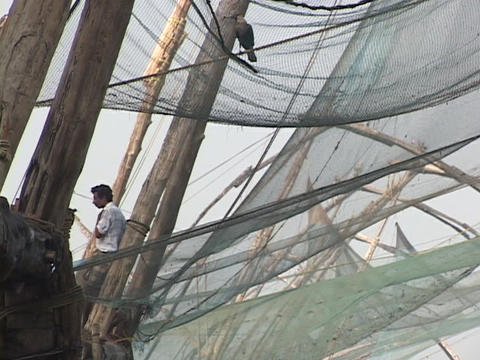 A man lounges beside fishing nets hanging in Kerala, India Stock Video Footage