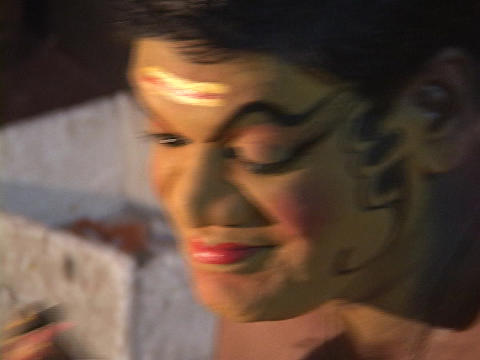 An actor applies his makeup for a Kathakali Dance performance Footage