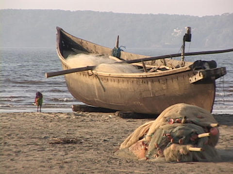 A woman stands near a beached fishing boat Footage