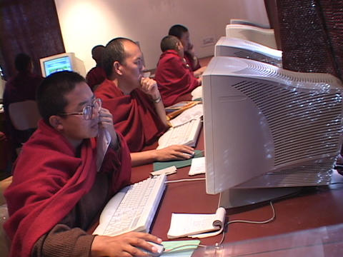 A group of Buddhist monks work on computers Footage