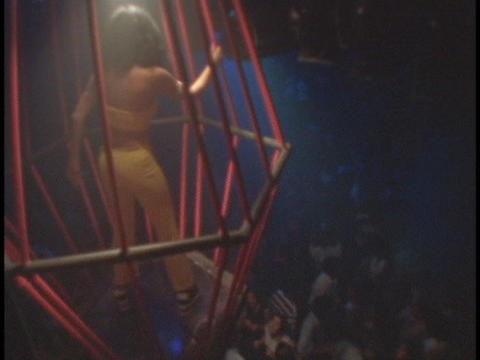A dancer performs in a cage above the dance floor Stock Video Footage