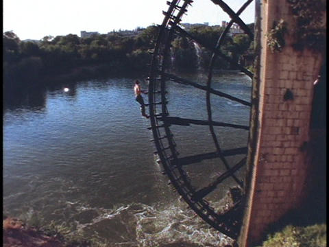 A young boy dives off a waterwheel and into the Orontes... Stock Video Footage