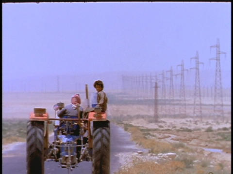 people ride in a tractor down a desert road Stock Video Footage