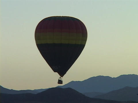 A hot air balloon floats over mountains Stock Video Footage