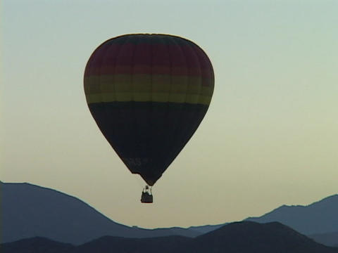 A hot air balloon floats over mountains Footage