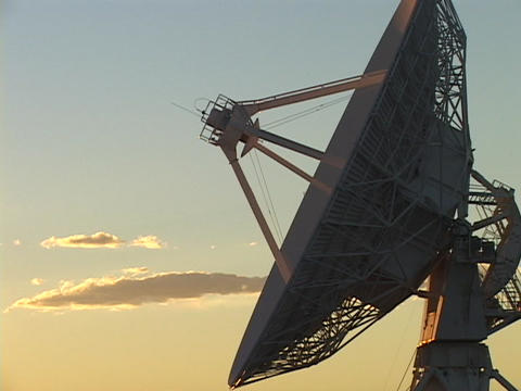 A golden sky lights the high points of a satellite dish at the Very Large Array of radio telescopes Footage