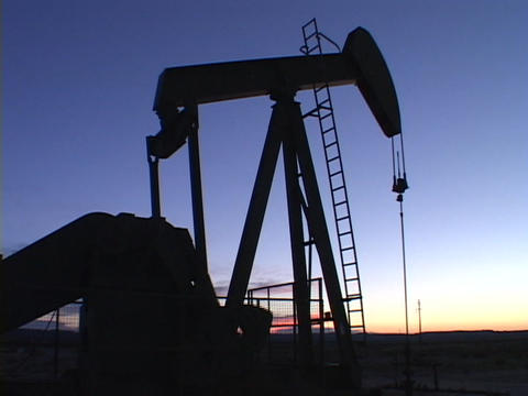 A pumping oil well stands in silhouette against the blue sky Footage