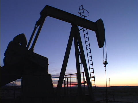 A pumping oil well stands in silhouette against the blue sky Stock Video Footage
