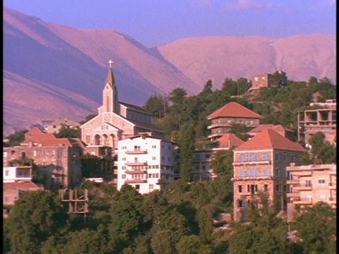 A village lies beneath mountains Stock Video Footage
