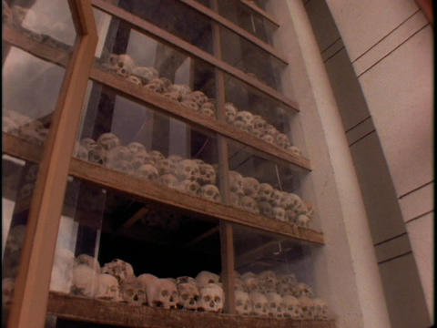 A man stands in front of Killing Fields Pyramid of Skulls... Stock Video Footage
