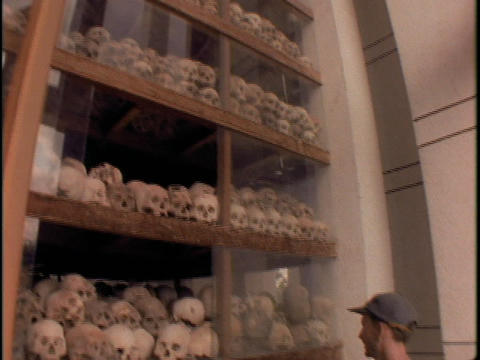 A man stands in front of Killing Fields Pyramid of Skulls in Khmer Rouge, Cambodia Footage